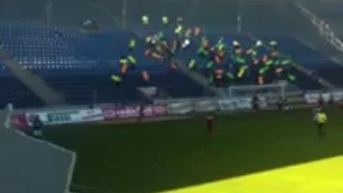 Des supporters indiquent le but à leur équipe avec des flèches géantes